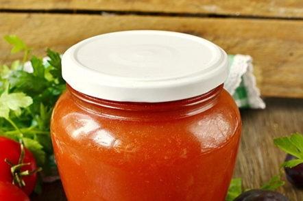 Ketchup prêt de prunes et de tomates pour l'hiver à la maison